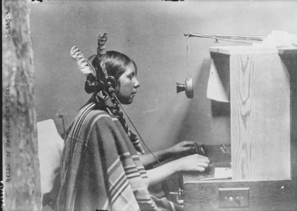 "Telephone operators worked at hotels as well as at exchanges. Photographed here is Helen (last name unknown), an operator at Many Glacier Hotel in Glacier National Park in 1925. At the time, park concessionaires often required their Blackfeet employees–including bus drivers and telephone operators—to dress in ""traditional"" clothing to appeal to eastern tourists. Bain News Service, Library of Congress Prints and Photographs Division Washington, D.C."